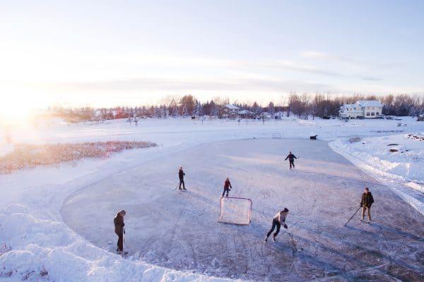 Packe deine Sachen in eine Schlittschuhtasche und gehe Eislaufen. Kinder spielen Eishockey.
