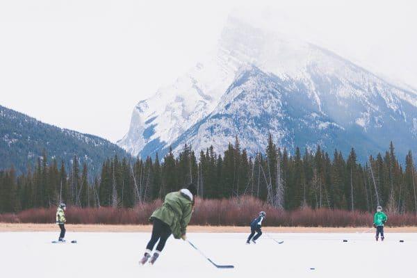 Eishockey spielende Kinder auf einem zugefrorenen See mit Bergkulisse.